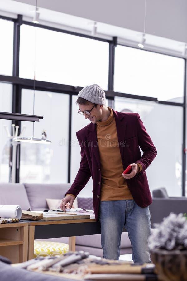 Diseñador de sexo masculino de lujo atractivo que comprueba los papeles en el escritorio de oficina fotografía de archivo libre de regalías