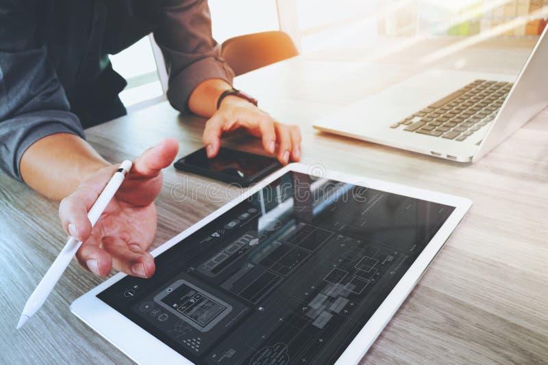 Diseñador del sitio web que trabaja el ordenador portátil digital de la tableta y del ordenador foto de archivo