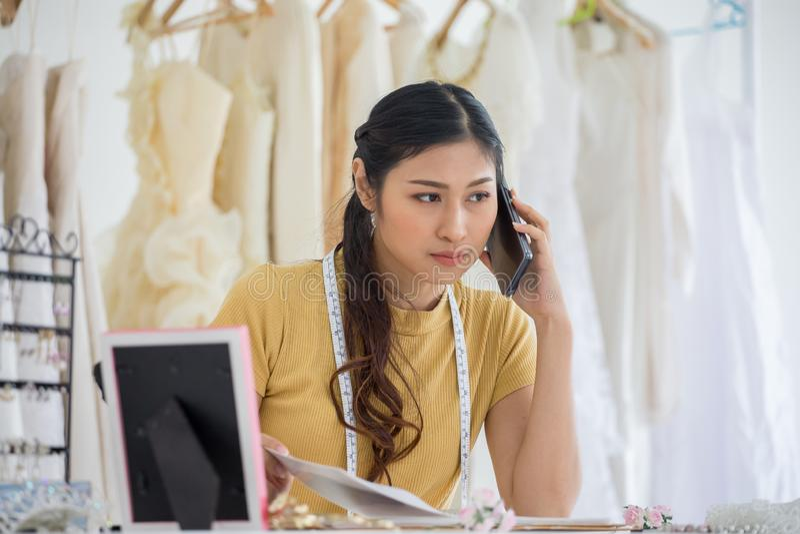 Diseñador del vestido de boda que trabaja con el teléfono elegante en casarse el salón de la tienda de la moda foto de archivo libre de regalías