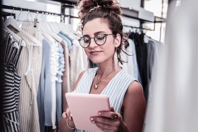 Diseñador elegante de moda con el estilo de plata del clavo que sostiene su tableta rosada fotografía de archivo