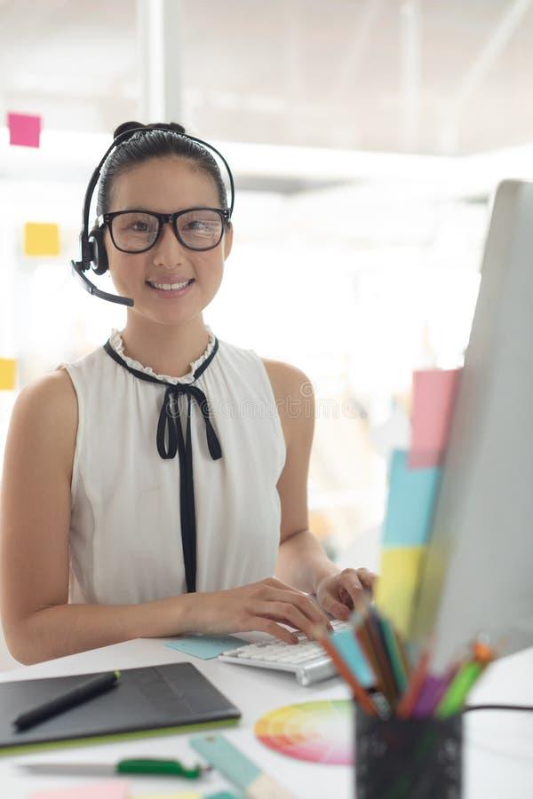 Diseñador gráfico de sexo femenino en las auriculares que miran la cámara mientras que trabaja en el escritorio en una oficina mo imagenes de archivo