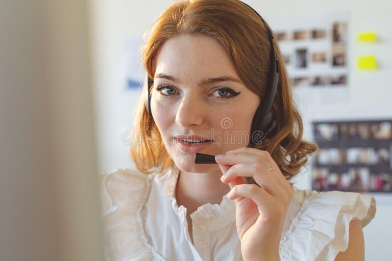 Diseñador gráfico de sexo femenino que habla en el auricular en oficina imagen de archivo libre de regalías