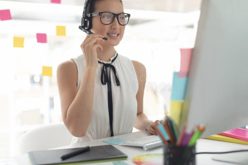 Diseñador gráfico de sexo femenino que habla en las auriculares en el escritorio en una oficina moderna foto de archivo