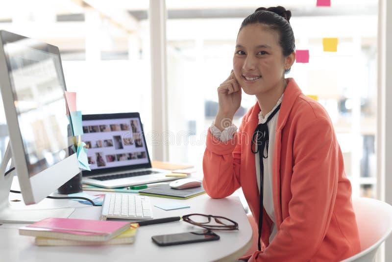 Diseñador gráfico de sexo femenino que mira la cámara en el escritorio en una oficina moderna imágenes de archivo libres de regalías