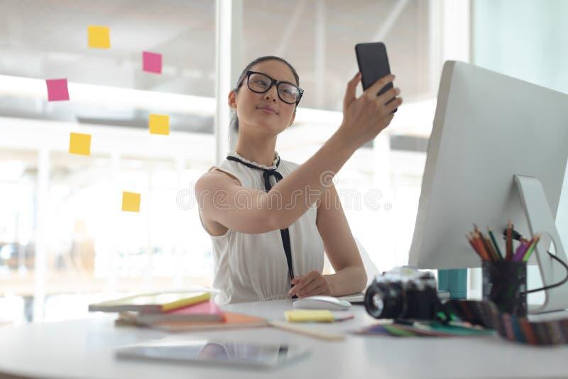 Diseñador gráfico de sexo femenino que toma el selfie con el teléfono móvil en el escritorio en una oficina moderna foto de archivo