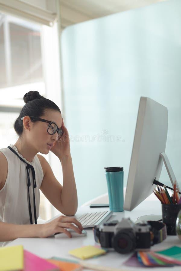 Diseñador gráfico de sexo femenino que trabaja en el ordenador en el escritorio en una oficina moderna fotos de archivo libres de regalías