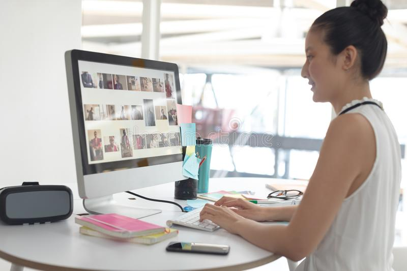 Diseñador gráfico de sexo femenino que trabaja en el ordenador en el escritorio en una oficina moderna imagen de archivo