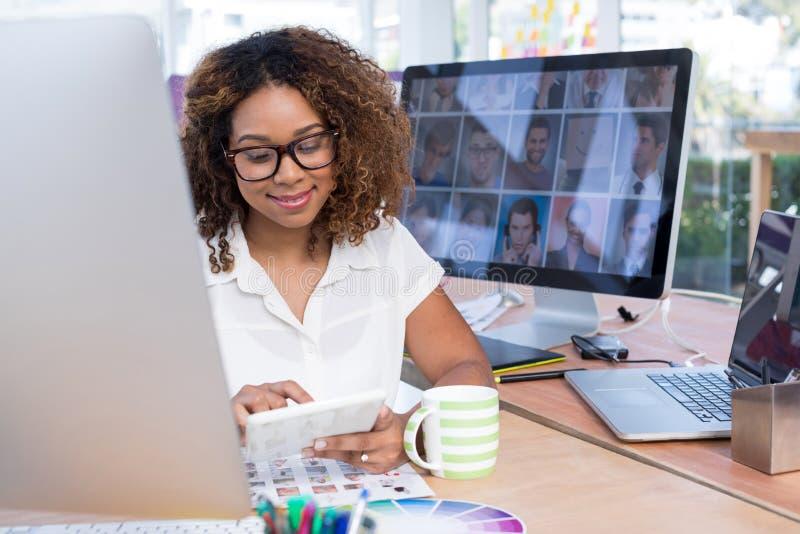 Diseñador gráfico de sexo femenino que usa la tableta digital en oficina fotografía de archivo