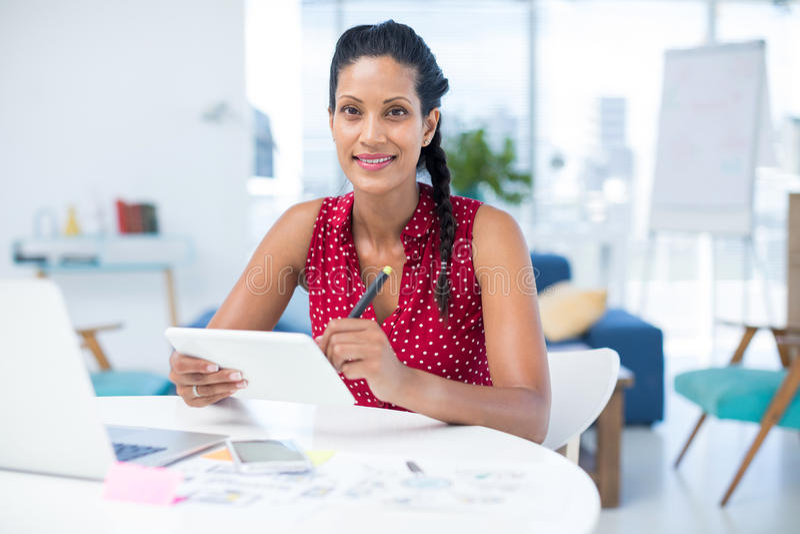 Diseñador gráfico de sexo femenino que usa la tableta gráfica en el escritorio imagen de archivo