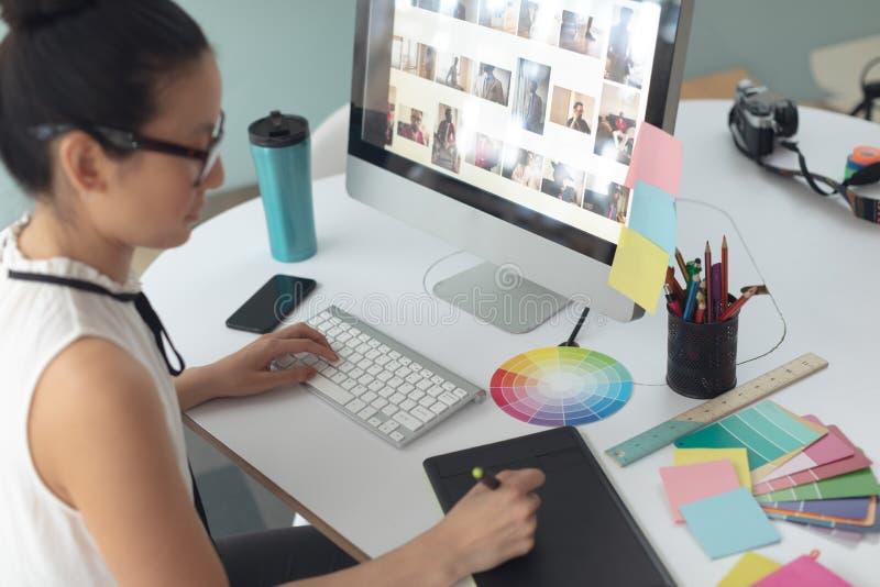 Diseñador gráfico de sexo femenino usando la tableta gráfica en el escritorio en una oficina moderna imagen de archivo