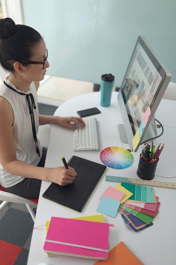 Diseñador gráfico de sexo femenino usando la tableta gráfica en el escritorio en una oficina moderna foto de archivo libre de regalías