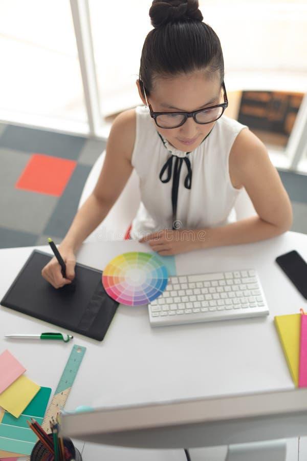 Diseñador gráfico de sexo femenino usando la tableta gráfica en el escritorio en una oficina moderna imágenes de archivo libres de regalías