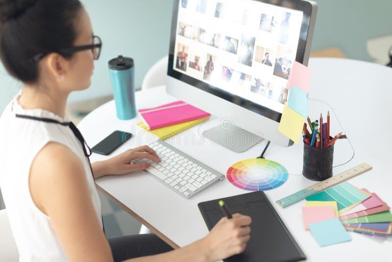 Diseñador gráfico de sexo femenino usando la tableta gráfica en el escritorio en una oficina moderna imagen de archivo libre de regalías