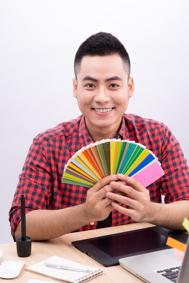 Diseñador gráfico de sexo masculino asiático feliz que sostiene la fan del color en su mano fotos de archivo