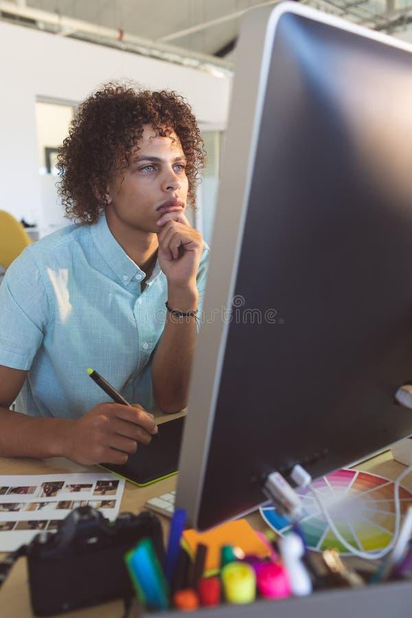 Dise?ador gr?fico de sexo masculino con la mano en la barbilla imagen de archivo libre de regalías