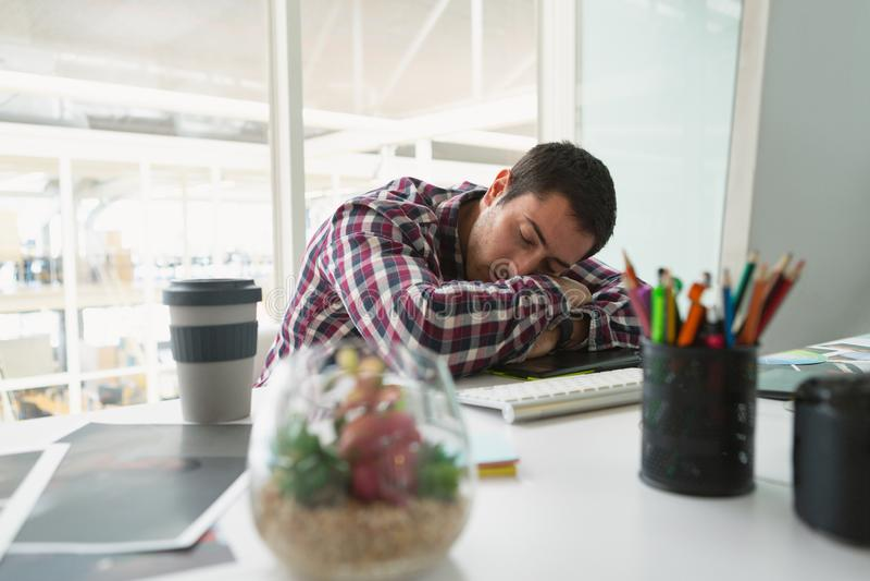 Diseñador gráfico de sexo masculino que duerme en el escritorio en oficina fotos de archivo