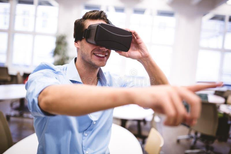 Diseñador gráfico de sexo masculino que gesticula mientras que usa las auriculares de la realidad virtual imágenes de archivo libres de regalías