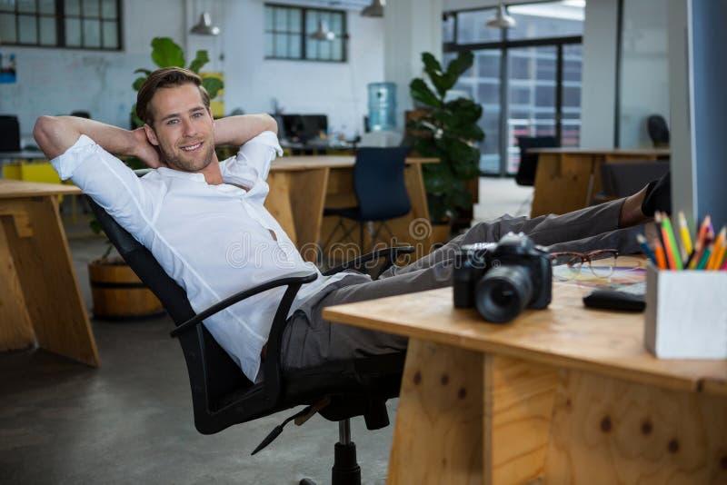 Diseñador gráfico de sexo masculino sonriente que se relaja en la silla imagenes de archivo