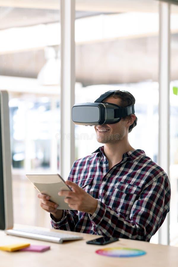 Diseñador gráfico de sexo masculino usando las auriculares de la realidad virtual mientras que trabaja en la tableta digital en e fotos de archivo