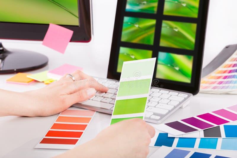Diseñador gráfico en el trabajo. Muestras del color. imagen de archivo libre de regalías