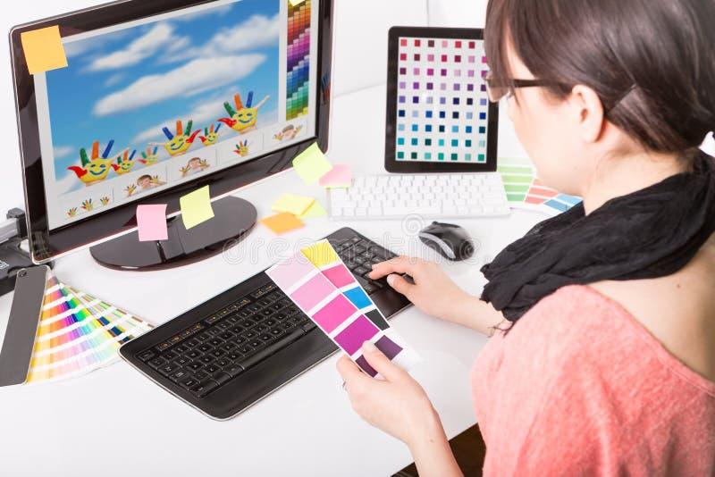 Diseñador gráfico en el trabajo Muestras del color imagen de archivo
