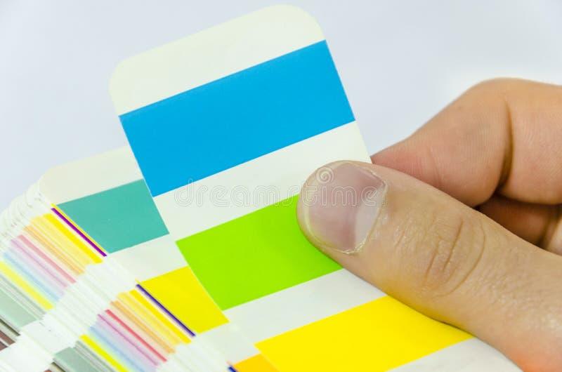 Diseñador gráfico que trabaja con la paleta del pantone en estudio imagen de archivo