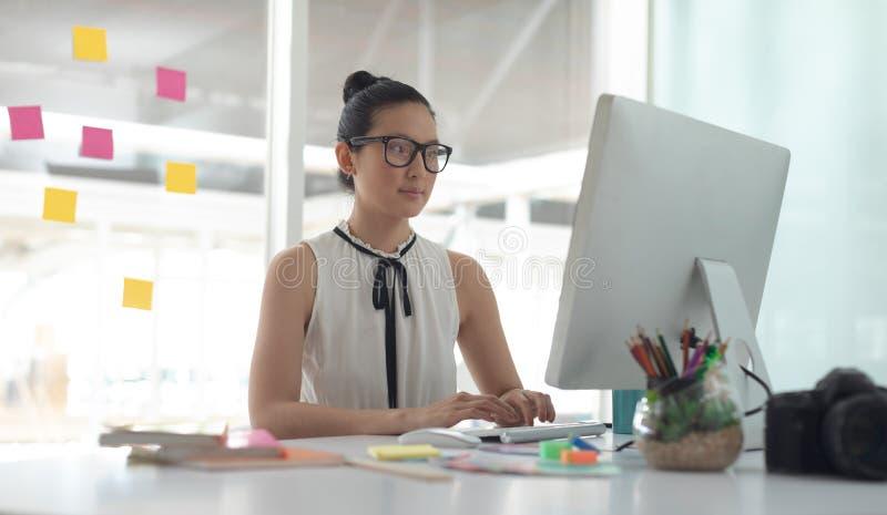 Diseñador gráfico que trabaja en el ordenador en el escritorio en una oficina moderna imagen de archivo