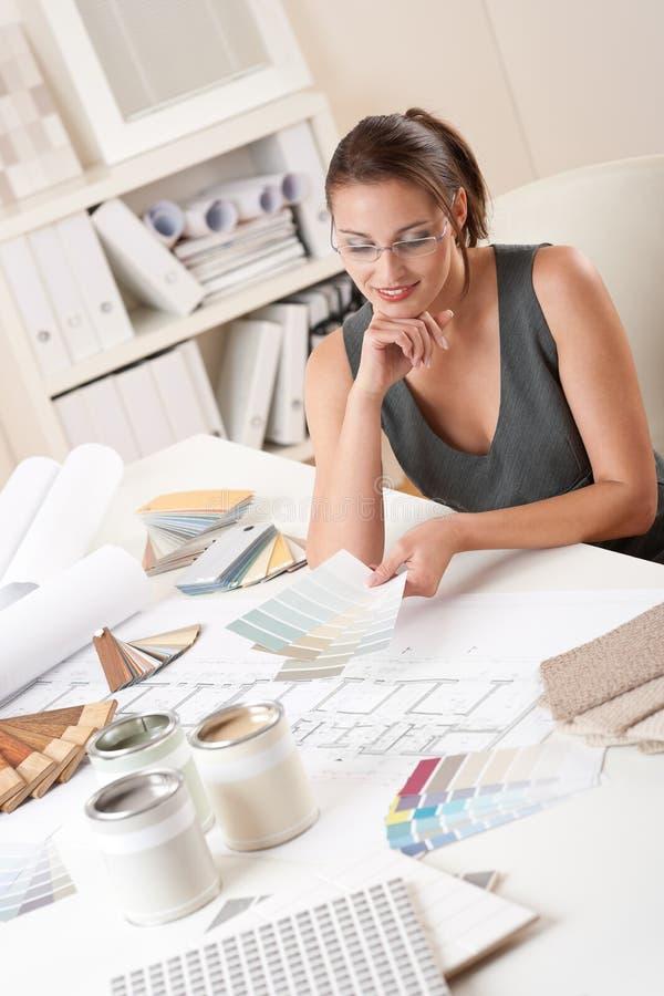 Diseñador interior de sexo femenino que trabaja con muestra del color foto de archivo