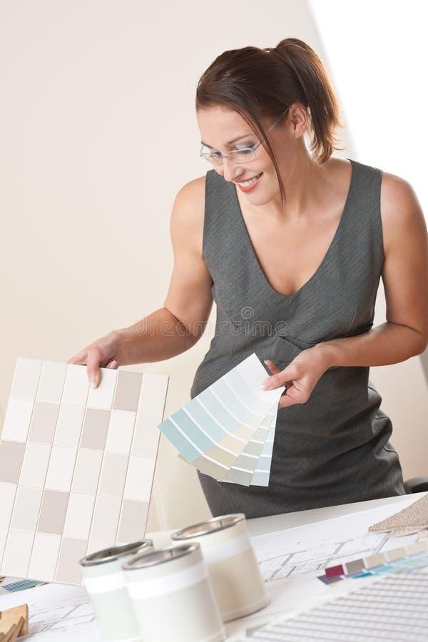 Diseñador interior de sexo femenino que trabaja con muestra del color imagen de archivo