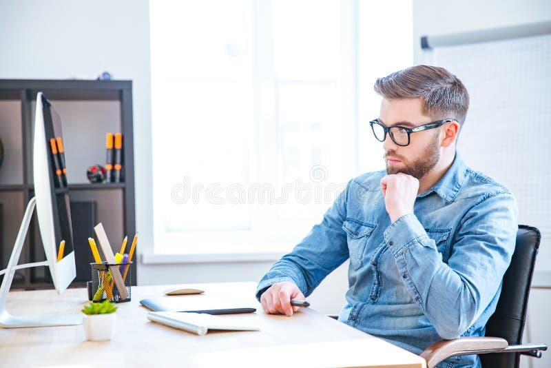 Diseñador pensativo que usa la tableta gráfica y el ordenador foto de archivo