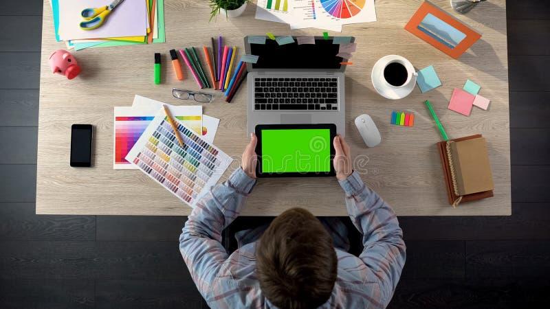 Diseñador que comprueba el correo en la tableta con la letra que espera de la pantalla verde para con orden fotografía de archivo
