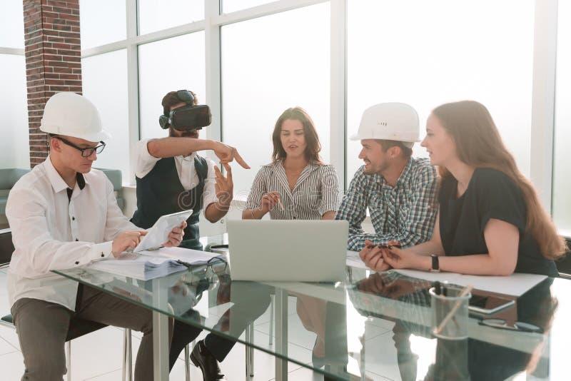 Diseñador que lleva los vidrios de la realidad virtual en una reunión con el equipo del negocio imágenes de archivo libres de regalías
