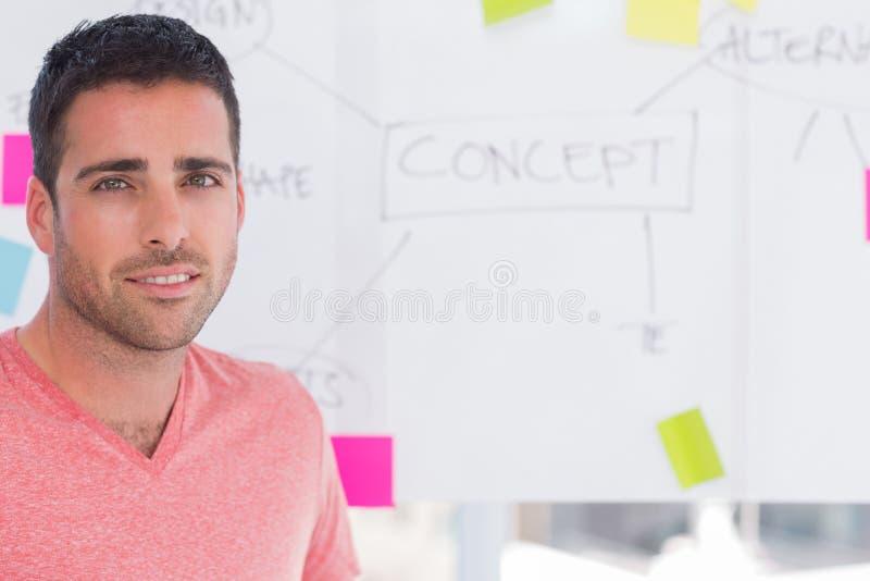Diseñador que se coloca delante de whiteboard imagen de archivo