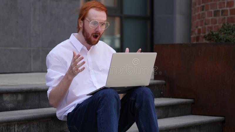 Diseñador que se pregunta Using Laptop mientras que se sienta en las escaleras fuera de la oficina fotos de archivo