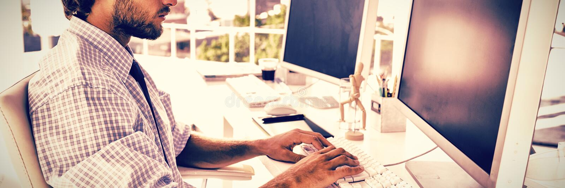 Diseñador que se sienta en su escritorio y trabajo fotos de archivo libres de regalías