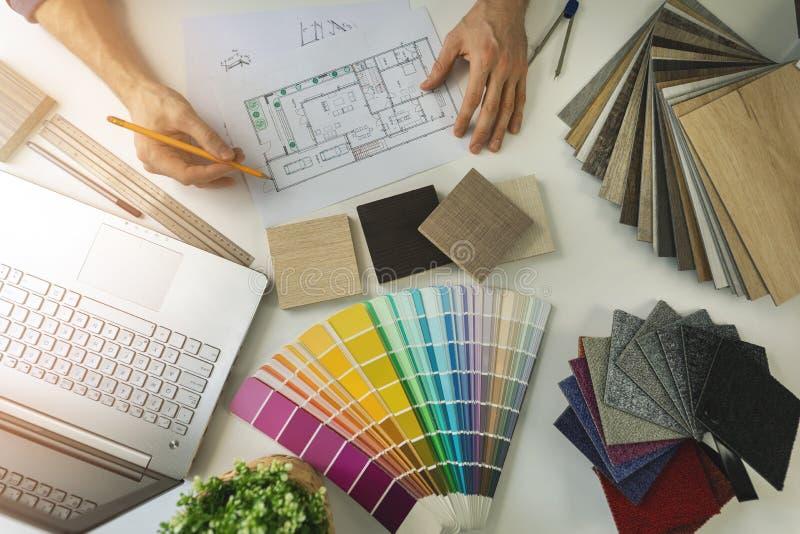 diseñador que trabaja en la oficina haciendo la selección de muebles y materiales de suelos de muestras para el proyecto de diseñ foto de archivo