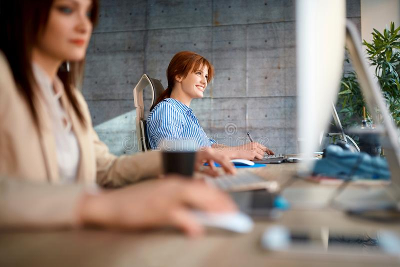 Diseñador sonriente de la mujer en el trabajo que trabaja en el ordenador para el nuevo proje imagenes de archivo