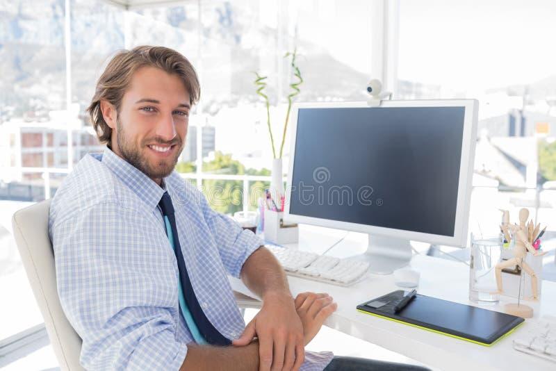 Diseñador sonriente que se sienta en su escritorio foto de archivo libre de regalías