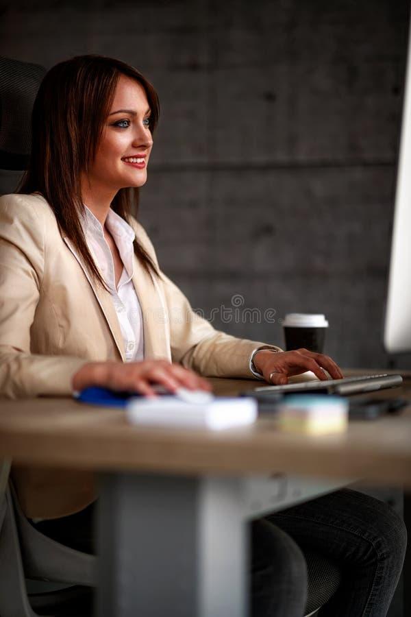 Diseñador sonriente que usa el ordenador en oficina foto de archivo libre de regalías