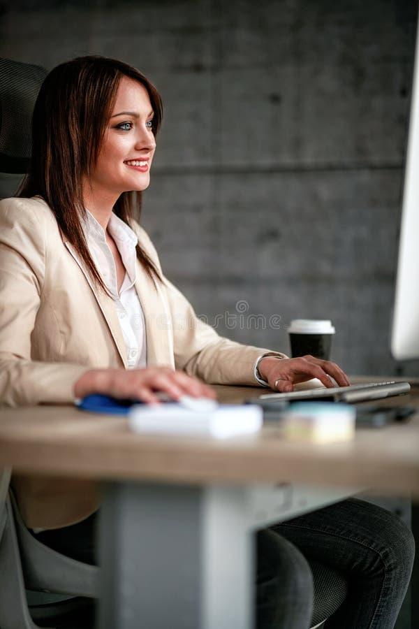 Diseñador sonriente que usa el ordenador en oficina fotografía de archivo libre de regalías