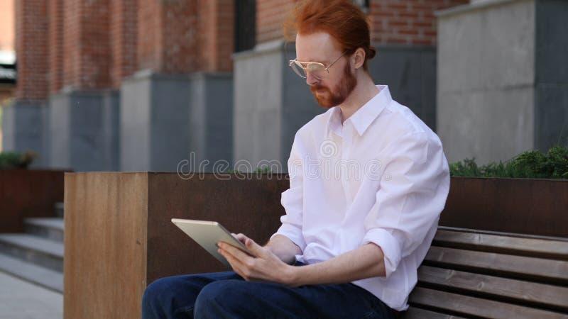 Diseñador Using Tablet Computer mientras que se coloca afuera fotografía de archivo libre de regalías