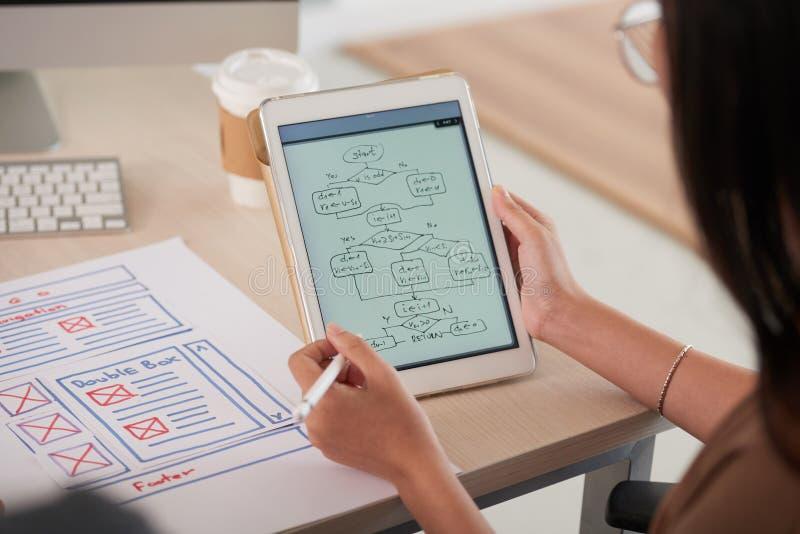 Diseñador web de sexo femenino que estudia el organigrama en la tableta foto de archivo libre de regalías
