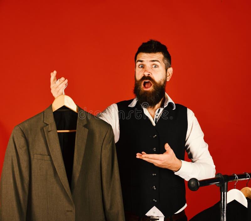 Diseñador y traje en la suspensión de ropa Hombre con la barba fotos de archivo libres de regalías