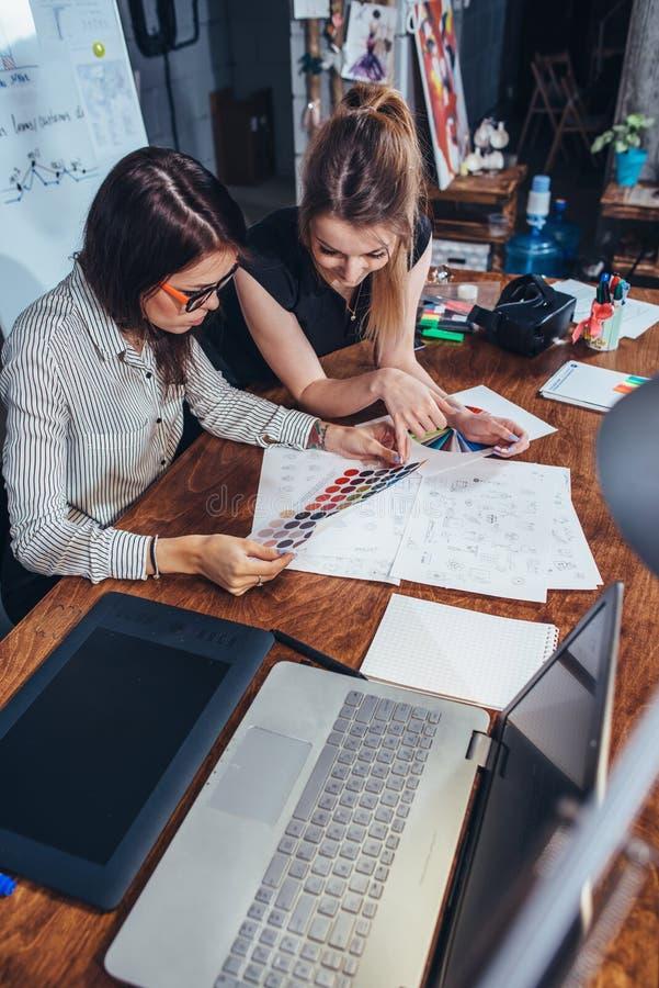 Diseñadores gráficos de sexo femenino jovenes que se sientan en el escritorio con el ordenador portátil, las cartas de color y al fotografía de archivo