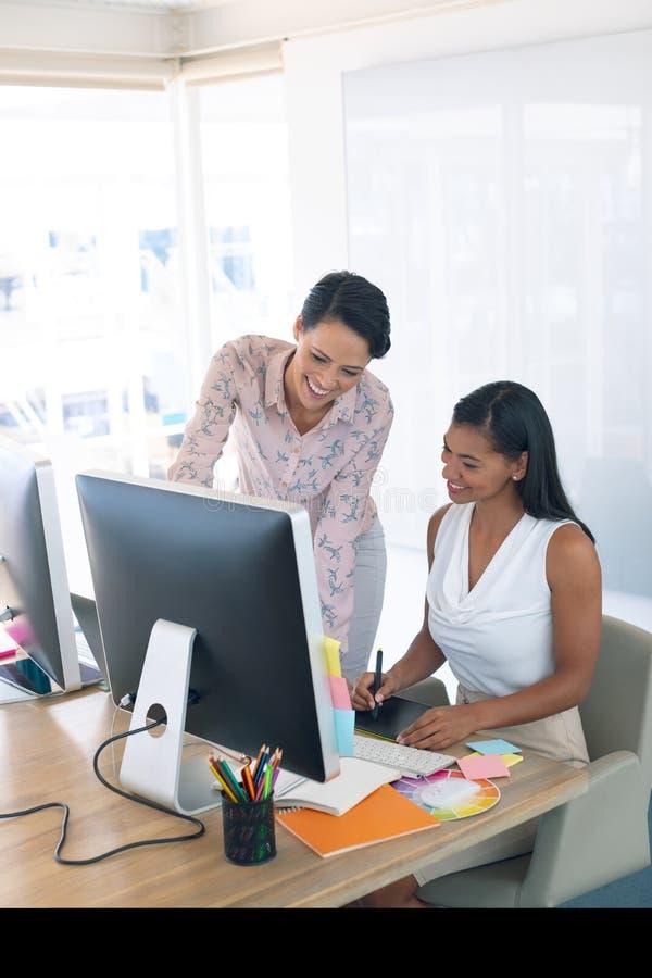 Diseñadores gráficos de sexo femenino que discuten en el ordenador en el escritorio en una oficina moderna foto de archivo