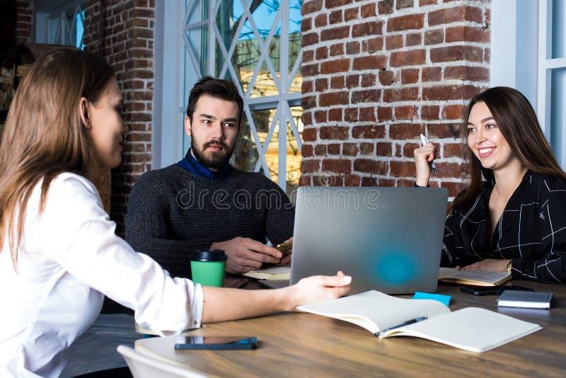 Diseñadores web profesionales del hombre y de las mujeres que tienen colaboraciones, hablando de inicio imagen de archivo libre de regalías