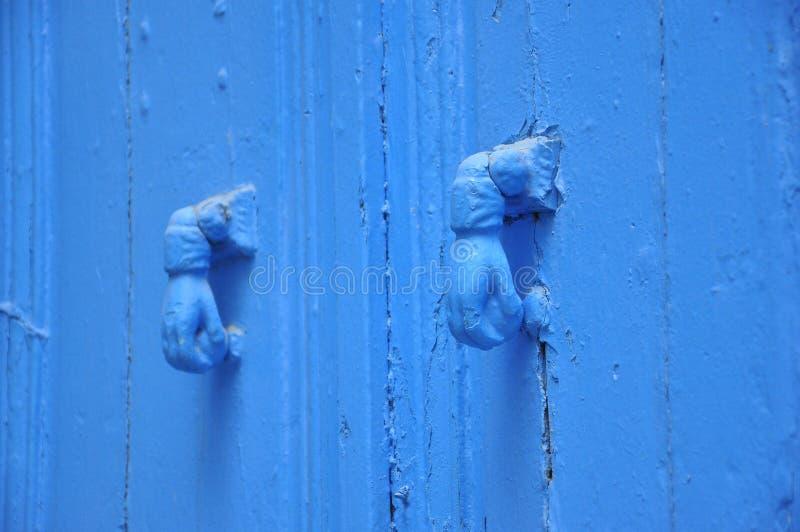 Diseño azul de la mano de dos golpeadores, puerta azul tunecina fotografía de archivo