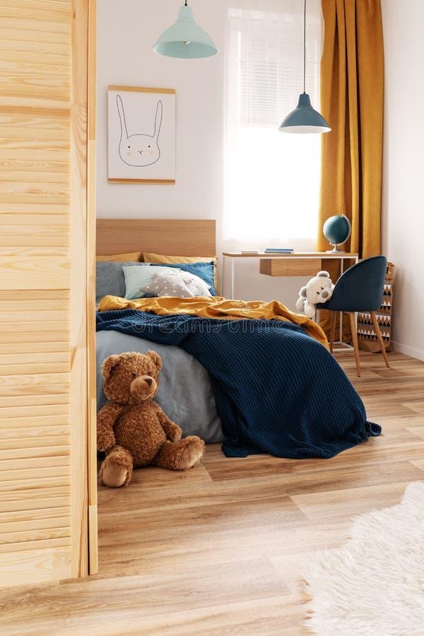 Diseño blanco, de madera, azul y anaranjado en interior brillante del dormitorio imagenes de archivo