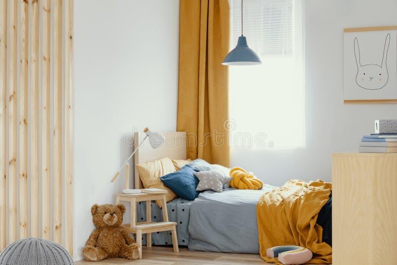 Diseño blanco, de madera, azul y anaranjado en interior brillante del dormitorio imágenes de archivo libres de regalías