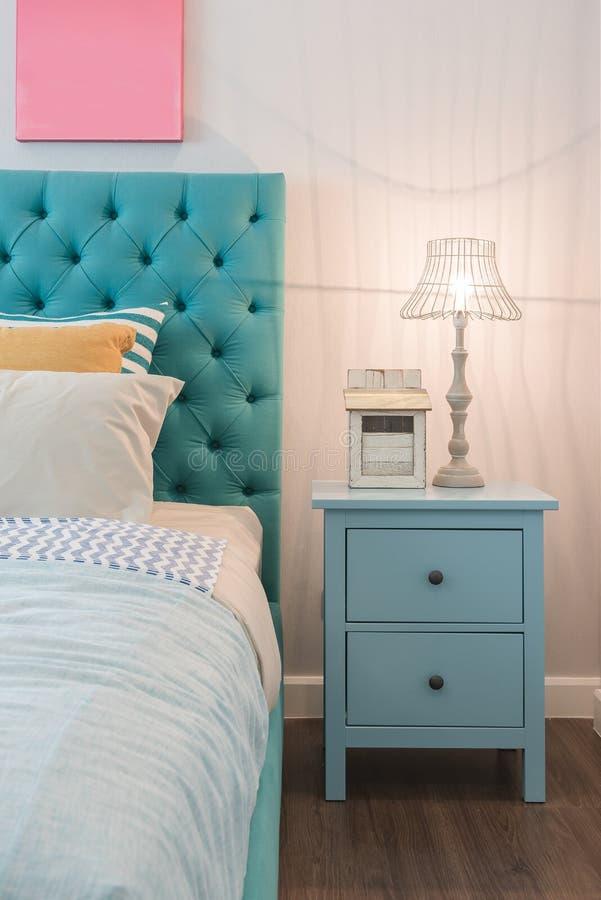 Diseño colorido moderno del dormitorio con la lámpara en la tabla azul imágenes de archivo libres de regalías